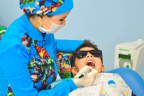 A dentist cleans a boy's teeth while he reclines with his mouth open while wearing sunglasses