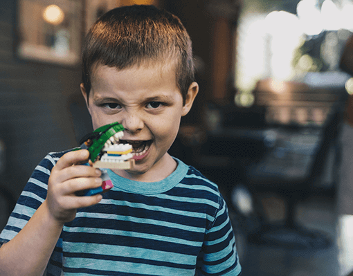 A boy plays with a lego jaw with large teeth