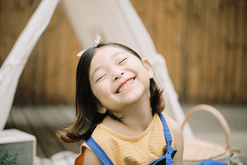 A young girl with a bow in her hair shows her teeth while smiling